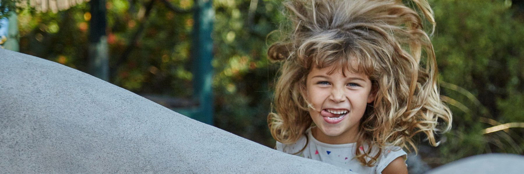 A photo of a young girl with a wild hair and a big smile.